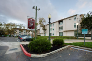 """Camera pole, banner reads """"Oak Village Apartments Leasing Office arrow pointing to right 510-835-4836"""", parking lot, reserved parking space"""
