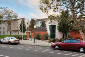 exterior of front entrance, angular building, sidewalk, Oak Village 801 14th Street sign