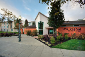 exterior of front entrance, angular building, sidewalk, Oak Village 801 14th Street sign