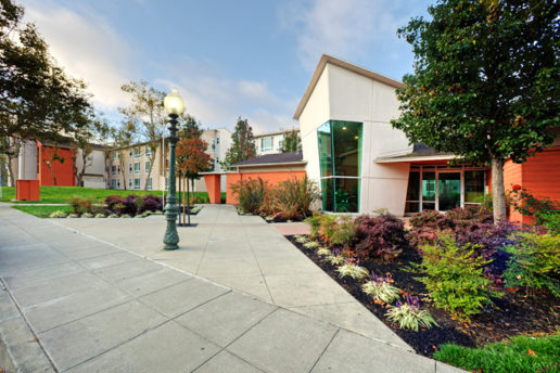 Front entrance of Oak Village lobby, sidewalks, and light post