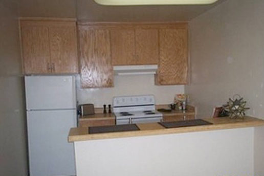 kitchen with brown cabinets, white appliances, breakfast bar
